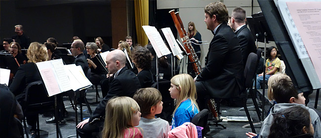 Students selected by their teachers sit on stage among the orchestra musicians